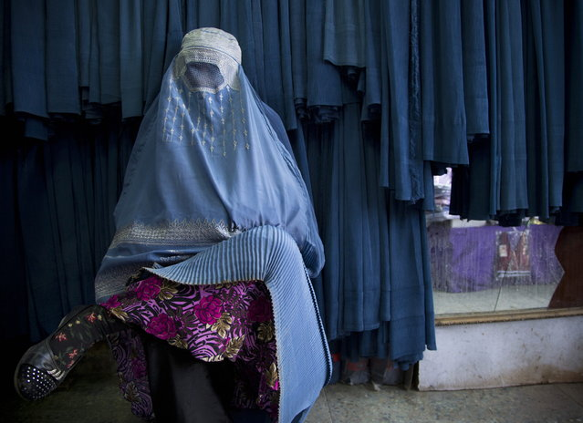 In this Thursday, April 11, 2013 photo, an Afghan woman waits to get in line to try on a new burqa at a shop in the old town of Kabul, Afghanistan. (Photo by Anja Niedringhaus/AP Photo)