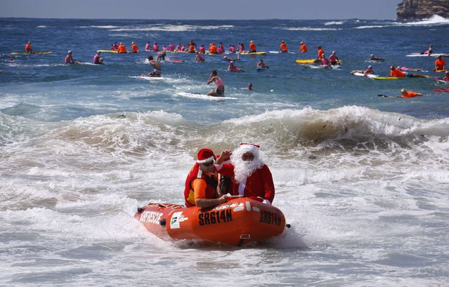 A man dressed as Santa Claus arrives in an inflatable rescue boat (IRB), as part of Christmas celebrations for the Coogee Surf Lifesaving Club, at Sydney's Coogee Beach December 14, 2014. (Photo by David Gray/Reuters)