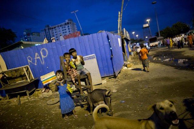 Children of street venders eat a roadside meal as street dogs walk around Yangon, Myanmar, Wednesday, November 4, 2015. (Photo by Gemunu Amarasinghe/AP Photo)