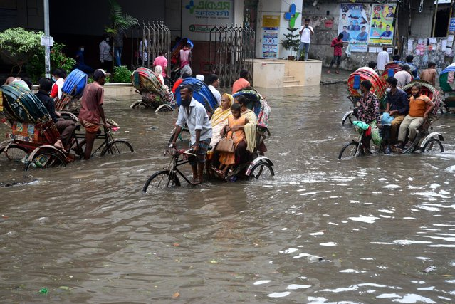 Vehicles try driving and citizens are walking through the water logging Dhaka streets in Bangladesh, on October 12, 2020. Heavy monsoon downpour caused extreme water logging in most areas of Dhaka city, Bangladesh. Roads were submerged making travel slow and dangerous. (Photo by Mamunur Rashid/NurPhoto via Getty Images)