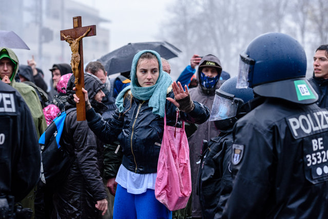 A woman with a large cross decorated with a Jesus figure during the use of water cannons by the police after heterogeneous groups around Corona deniers, conspiracy theorists and right-wing extremists called for blocking access to German Government Buildings in Berlin, Germany on November 18, 2020. Both the Bundestag and the Bundesrat vote on planned new regulations of the infection protection law. (Photo by Jan Scheunert/ZUMA Wire/Rex Features/Shutterstock)
