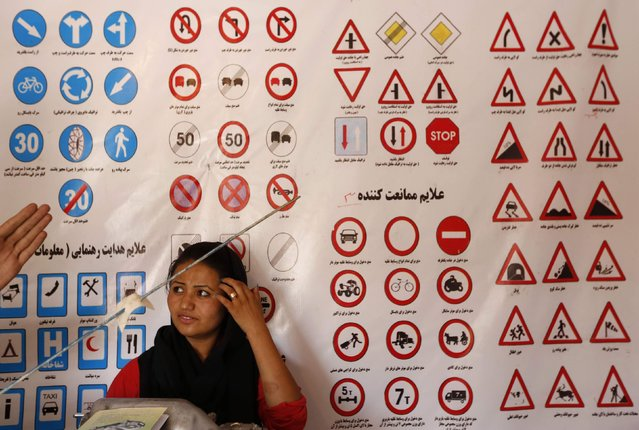 A woman listens to an instructor (unseen) who explains traffic signs at a driving school in Kabul August 11, 2014. (Photo by Mohammad Ismail/Reuters)