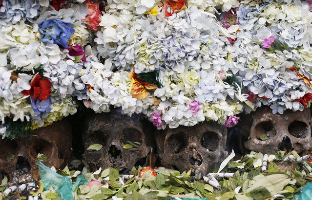 """Human skulls or """"natitas"""" crowned with flowers are surrounded by offerings of coca leaves, flower petals and cigarettes, outside the Cementerio General chapel during the Natitas Festival, in La Paz, Bolivia, Sunday, November 8, 2015. Although some natitas have been handed down through generations, many are from unnamed, abandoned graves that are cared for and decorated by faithful who use them as amulets believing they serve as protection. (Photo by Juan Karita/AP Photo)"""