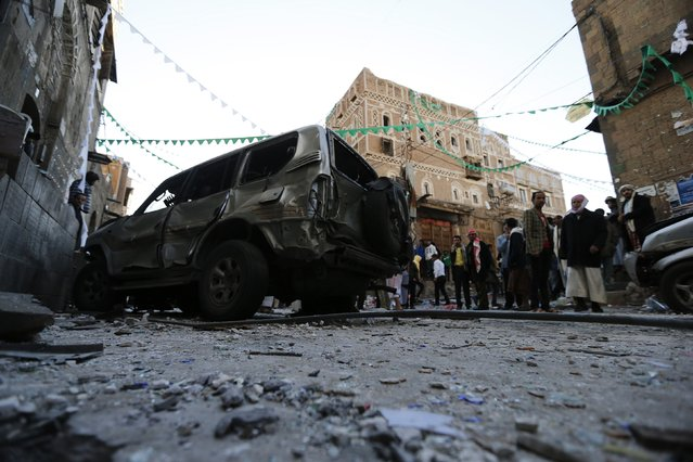 People gather at the site of a bomb explosion in Sanaa December 23, 2014. (Photo by Khaled Abdullah/Reuters)