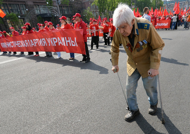 A veteran of World War II walks ahead the Ukrainian Communists march and rally marking May Day in the center of Kiev. (Photo by Sergei Supinsky/Getty Images)