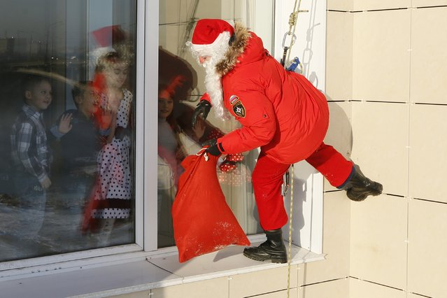 """Alexei Trifonov, a member of the """"Rescuer"""" state regional service, dressed as Santa Claus, looks through a window as he prepares to congratulate employees of the Russian Emergencies Ministry and their children ahead of New Year and Christmas celebrations in Krasnoyarsk, Siberia, December 24, 2014. (Photo by Ilya Naymushin/Reuters)"""