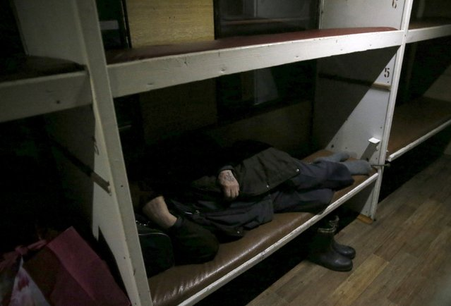 A man sleeps inside a train travelling to Sankin, in Sverdlovsk region, Russia October 16, 2015. The narrow-gauge railway is the main transport connection between seven rural settlements in Alapayevsk District. The train from Alapayevsk to Sankin usually has three carriages, two second class sleeping carriages and one sitting carriage. The train makes its journey four times per week. (Photo by Maxim Zmeyev/Reuters)