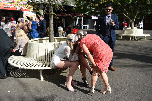 Race goers whisper to each other after the Geelong Cup on Geelong Cup day at Geelong Racecourse in Melbourne, Wednesday, October 19, 2016. (Photo by Tracey Nearmy/AAP Image)