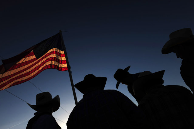 The American flag is surrounded by cowboys taking part in a BLM Bull and Rodeo Company event at Oakland Heights Farm on Saturday June 14, 2014 in Gordonsville, VA. (Photo by Matt McClain/The Washington Post)