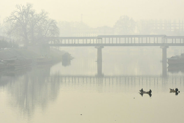 Boatmen row their boats in the waters of river Jhelum amid foggy condition in Srinagar on December 2, 2020. (Photo by Tauseef Mustafa/AFP Photo)