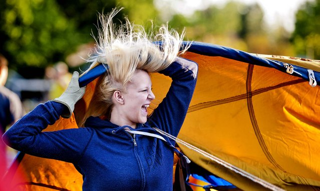 Mikaela Smith laughs and attempts to control some of her flying hair in front of the large fan used to begin inflating the envelope of the hot air balloon, Anonymous,  Friday morning, May 10, 2013 at Greenpark Elementary School in Walla Walla, Wash. during the 39th annual Walla Walla Hot Air Balloon Stampede. (Photo by Matthew Zimmerman Banderas/AP Photo/Walla Walla Union-Bulletin)