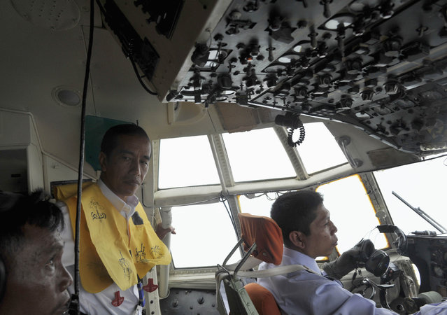 Indonesian President Joko Widodo (C) oversees the aerial search operation for missing AirAsia Flight QZ8501, on board a Hercules over the sea south of  Pangkalan Bun, central Kalimantan December 30, 2014 in this photo taken by Antara Foto. (Photo by Andika Wahyu/Reuters/Antara Foto)