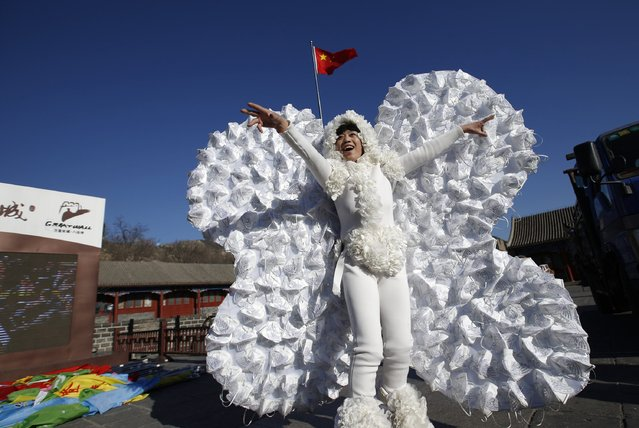 Chinese artist Kong Ning poses in a costume symbolizing a butterfly, which is decorated with 365 masks on its wings to represent the number of days in a year, during her performance art at the Badaling section of the Great Wall on the outskirts of Beijing January 1, 2015. (Photo by Kim Kyung-Hoon/Reuters)