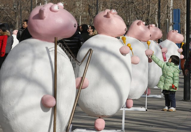A girl interacts with installations resembling sheep, put up as part of celebrations leading to the New Year, in Beijing December 29, 2014. 2015 is the Year of the Sheep, according to the Chinese calendar. (Photo by Kim Kyung-Hoon/Reuters)