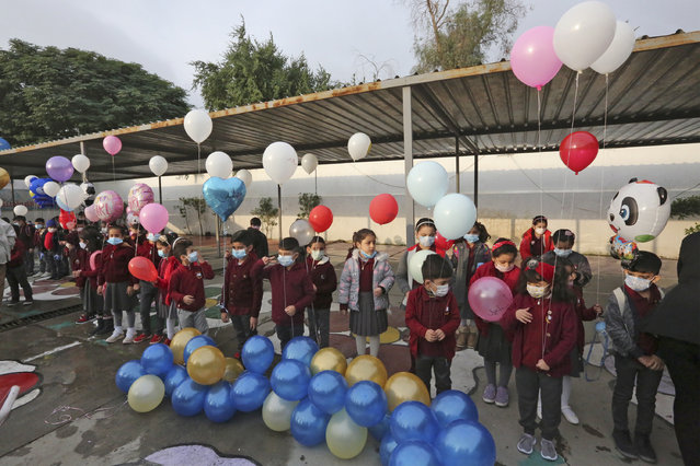 Iraqi pupils wearing protective masks hold balloons in their school yard on the first day of the new academic year, at Hariri primary school in the capital Baghdad, on November 29, 2020, amid the COVID-19 pandemic. Iraq's schools began a new academic year, after weeks of delay due to the coronavirus pandemic. Children will attend class in person once a week on rotating shifts, and will take online (distant learning) courses the rest of the week. (Photo by Sabah Arar/AFP Photo)