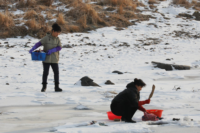 North Korean women are photographed from the Chinese side of the border near the town of Changbai, China as they wash clothes in the frozen Yalu River near the North Korean town of Hyesan, November 23, 2017. (Photo by Damir Sagolj/Reuters)