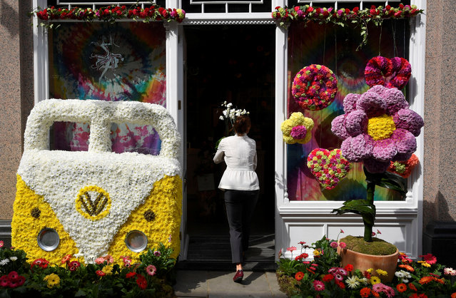A woman carries flowers into a florists which is participating in the Chelsea In Bloom festival in London, Britain on May 22, 2018. (Photo by Toby Melville/Reuters)