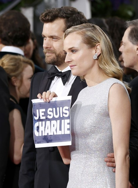 "Actress Diane Kruger holds a ""Je Suis Charlie"" sign referring to the attacks in Paris as she poses with actor Joshua Jackson at the 72nd Golden Globe Awards in Beverly Hills, California January 11, 2015. (Photo by Mario Anzuoni/Reuters)"