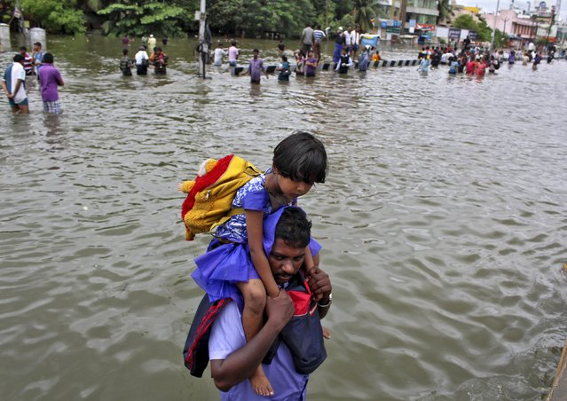 A man carries a girl through a flooded road in Chennai, India, December 2, 2015. (Photo by Reuters/Stringer)