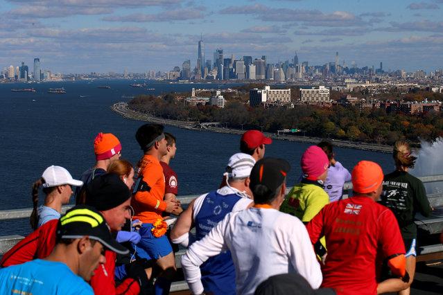 Manhattan is seen in the distance as runners cross the Verrazano–Narrows Bridge during the 2016 New York City Marathon in the Manhattan borough of New York City, NY, U.S. November 6, 2016. (Photo by Brendan McDermid/Reuters)