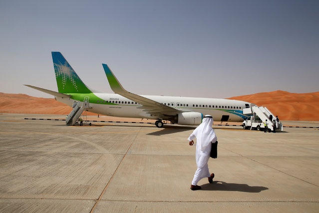 An Aramco employee walks towards an Aramco private plane at the private airport at Shaybah oilfield in the Empty Quarter, Saudi Arabia May 22, 2018. (Photo by Ahmed Jadallah/Reuters)