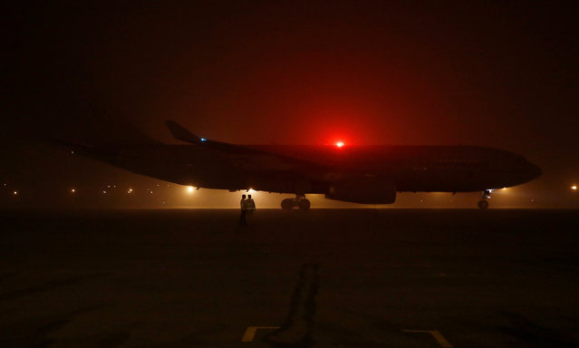 Airport staff stand as Britain's Prime Minister Theresa May's aircraft arrives amid the heavy smog at the airport in New Delhi, India, November 6, 2016. (Photo by Adnan Abidi/Reuters)