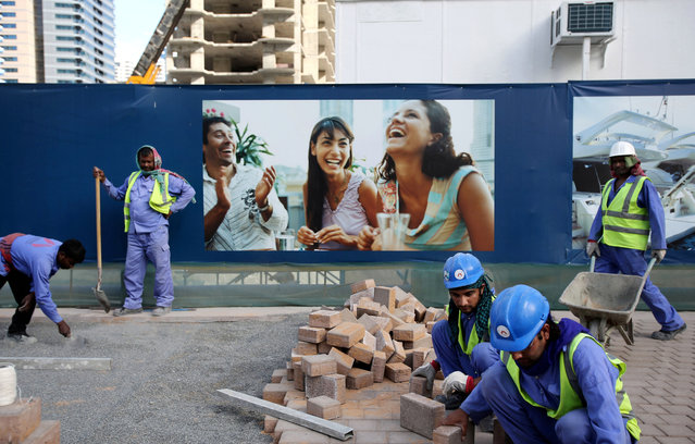 In this March 26, 2015 photo, laborers install paving stones in front of an advertisement for luxury real estate, in the Marina district of Dubai, United Arab Emirates. Armies of low-paid migrant workers, many of them from the Indian Subcontinent, leave behind families and travel to Dubai to build soaring towers like those in the Marina. While the wages they come for offer hope of a better life, they are far too meager for most to ever dream of calling the Marina they built home. (Photo by Kamran Jebreili/AP Photo)