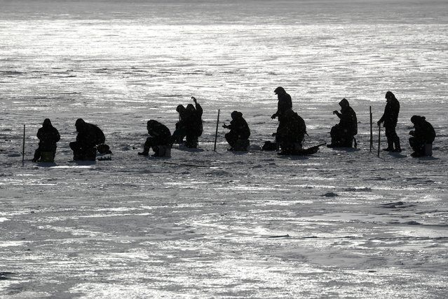 People fish on the frozen Dnipro river in Kyiv, Ukraine on February 15, 2021. (Photo by Valentyn Ogirenko/Reuters)