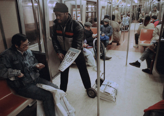 Barry Couliffe sells copies of the Daily News to an unidentified passenger on the subway in New York, Thursday, March 15, 1991. (Photo by Bebeto Matthews/AP Photo)