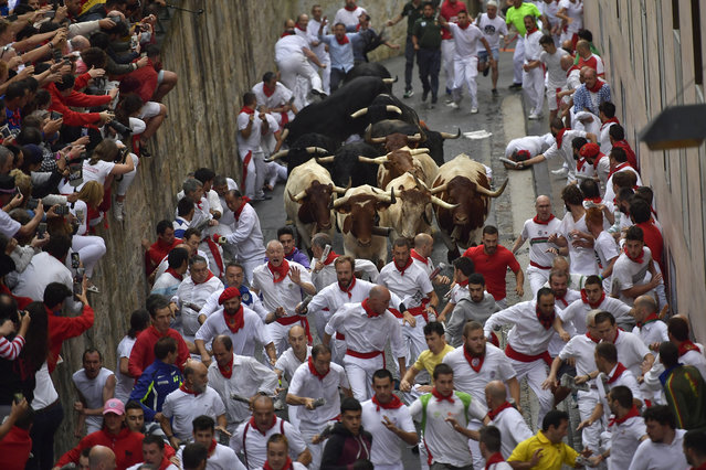 Revellers run next to Puerto de San Lorenzo's fighting bulls during the running of the bulls at the San Fermin Festival, in Pamplona, northern Spain, Saturday, July 7, 2018. Revellers from around the world flock to Pamplona every year to take part in the eight days of the running of the bulls. (Photo by Alvaro Barrientos/AP Photo)