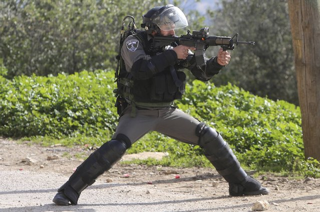 An Israeli border policeman points his weapon at Palestinian protesters during clashes following a protest against the nearby Jewish settlement of Qadomem, in the West Bank village of Kofr Qadom near Nablus January 23, 2015. (Photo by Abed Omar Qusini/Reuters)