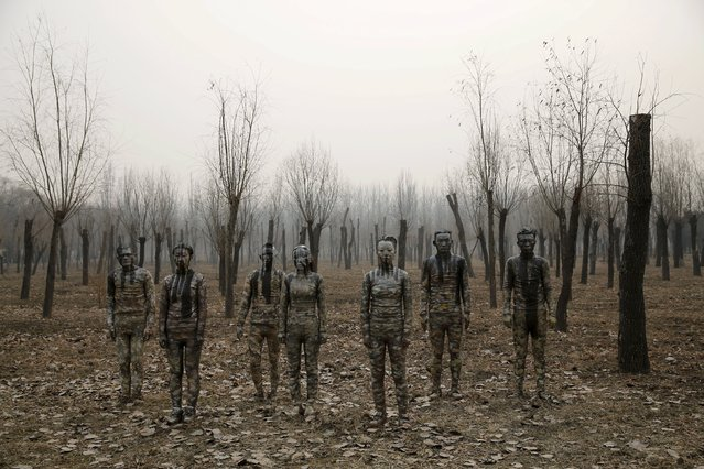 """Models painted in camouflage colours to blend in with the background pose for Chinese artist Liu Bolin's artwork """"Dongji"""", or Winter Solstice, on the second day after China's capital Beijing issued its second ever """"red alert"""" for air pollution, in Beijing, China, December 20, 2015. (Photo by Kim Kyung-Hoon/Reuters)"""