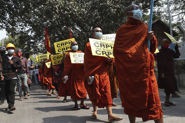 Monks hold signs as they march during an anti-coup protest in Mandalay, Myanmar, Saturday, March 6, 2021. (Photo by Reuters/Stringer)
