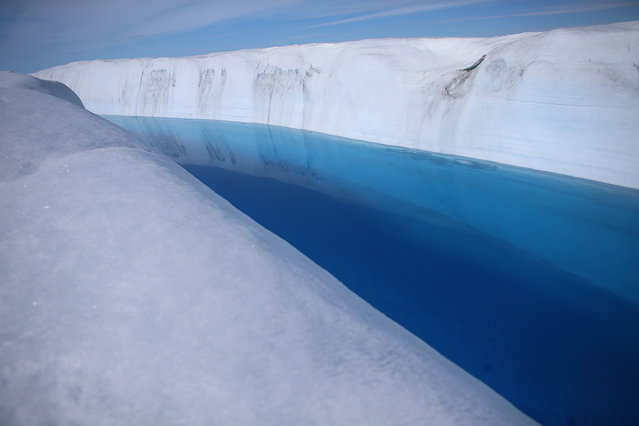 Meltwater stands on the surface of the glacial ice sheet, on July 17, 2013. (Photo by Joe Raedle/Getty Images via The Atlantic)