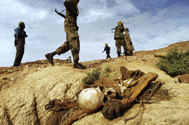Sudanese Liberation Army soldiers walk past a dead body left from an attack on civilians in the district of Farawiya, Darfur, August 24, 2004. Sixteen bodies lay in the surrounding ravines after men from five nearby villages were allegedly killed by Janjaweed militias backed by Sudanese government forces. (Photo by Lynsey Addario)