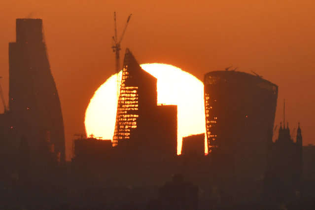 The sun is seen rising over skyscrapers in the City of London financial district in London, Britain, May 3, 2018. (Photo by Toby Melville/Reuters)