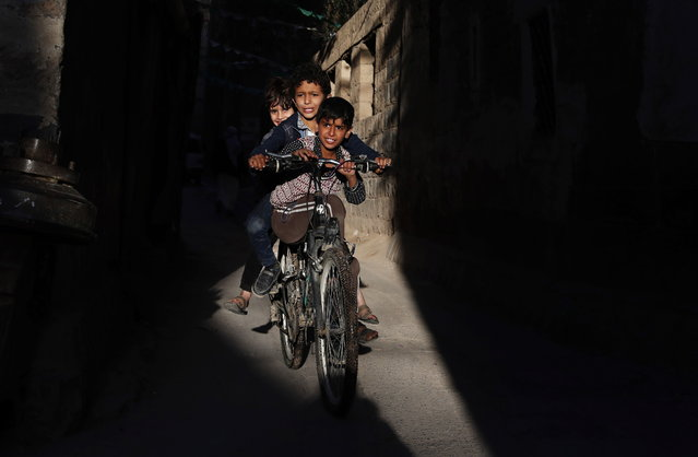 Yemeni children ride a bicycle through a narrow alley in the old city of Sana'a, Yemen, 21 January 2021. According to reports, the United Nations and aid agencies are urging the US administration of President Biden to revoke the designation of the Houthis movement in Yemen as a foreign terrorist organization, warning that could push the country into a humanitarian catastrophe and chill peace efforts. (Photo by Yahya Arhab/EPA/EFE)