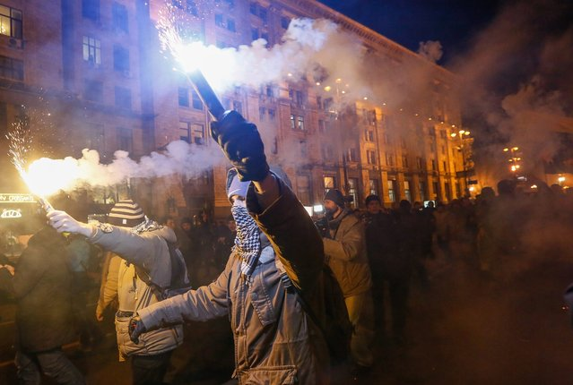 Activists and supporters of Ukrainian nationalist groups light flares during a rally to mark the third anniversary of the Euromaidan Revolution in downtown Kiev, Ukraine, 21 November 2016. (Photo by Roman Pilipey/EPA)