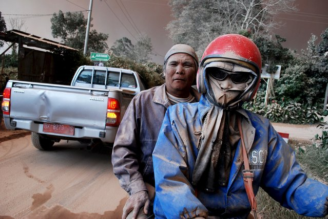 Residents with faces covered in ash ride on a motorcycle as Mount Sinabung volcano erupts, in Sukandebi village in Karo Regency, Indonesia's North Sumatra province, Indonesia June 13, 2015, in this photo taken by Antara Foto. (Photo by Rony Muharrman/Reuters/Antara Foto)