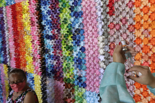 A health worker prepares a shot of the Sinovac vaccine for COVID-19 in front of a panel of origami lotus flowers, placed in honor of victims of the pandemic, at a health center in Brasilia, Brazil, Monday, March 29, 2021. According to the organizers, the flower panel is also a gesture of thanks to health professionals and of hope to those who are being vaccinated. (Photo by Eraldo Peres/AP Photo)