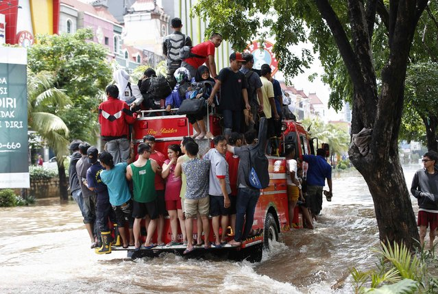 People ride on a fire truck through a flooded street after continuous heavy seasonal rains have flooded many parts of Jakarta February 10, 2015. (Photo by Darren Whiteside/Reuters)