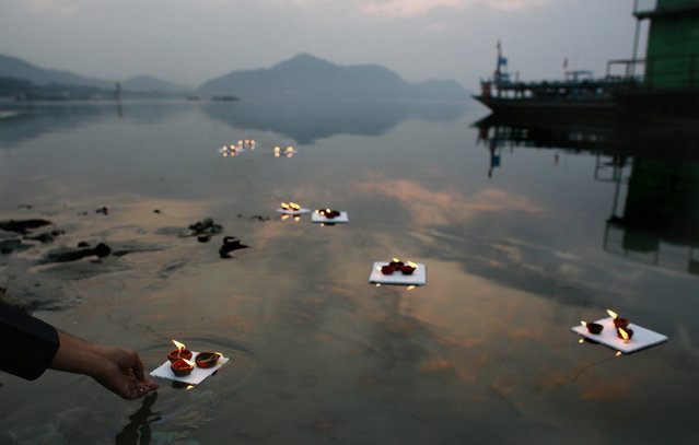 Indians float earthen lamps in the River Brahmaputra on the second day of a week day long kite festival in Gauhati, India, Saturday, January 2, 2016. (Photo by Anupam Nath/AP Photo)