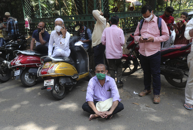 A man wearing mask sits on the road as he waits his turn for COVID-19 test outside a court in Mumbai, India, Monday, April 5, 2021. India reported its biggest single-day spike in confirmed coronavirus cases since the pandemic began Monday, and officials in the hard-hit state home to Mumbai are returning to the closure of some businesses and places of worship in a bid to slow the spread. (Photo by Rafiq Maqbool/AP Photo)