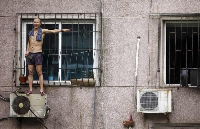A man, whose last name is Hou, gestures while holding a knife as he stands outside a window atop an air conditioner theatening to cut himself, in Anshan, Liaoning province August 26, 2013. (Photo by Reuters/Stringer)