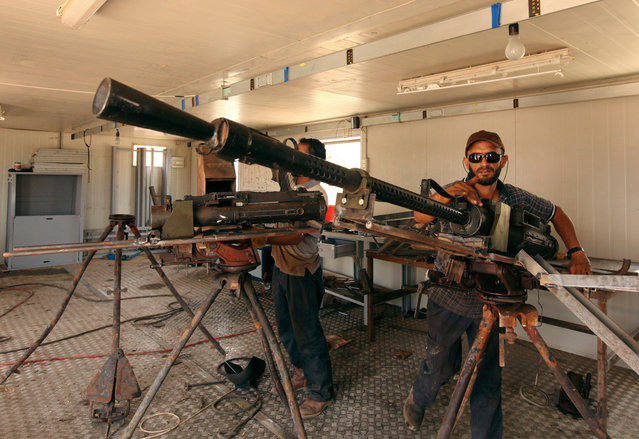 A rebel soldier repairs weapons captured from forces loyal to Libyan leader Muammar el-Qaddafi, at a workshop in Benghazi, on June 13, 2013. (Photo by Esam Al-Fetori/Reuters)