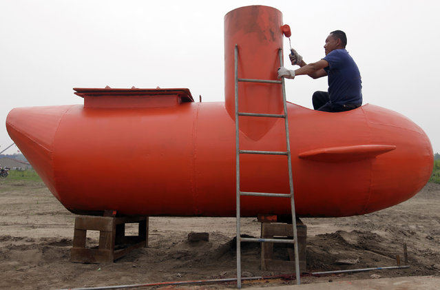 A worker paints a single-seater submarine designed by Zhang Wuyi and his fellow engineers at a shipyard in Wuhan, Hubei province May 7, 2012. Zhang, a 37-year-old local farmer, who is interested in scientific inventions, has made six miniature submarines with several fellow engineers, one of which was sold to a businessman in Dalian at a price of 100,000 yuan ($15,855) last October. The submarines, mainly designed for harvesting aquatic products, such as sea cucumber, have a diving depth of 20-30 metres, and can travel for 10 hours, local media reported. (Photo by Reuters/Stringer)