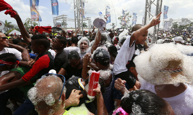 Bathed with suds, revelers dance in the street during Carnival celebrations in Panama City, Monday, February 16, 2015. (Photo by Arnulfo Franco/AP Photo)