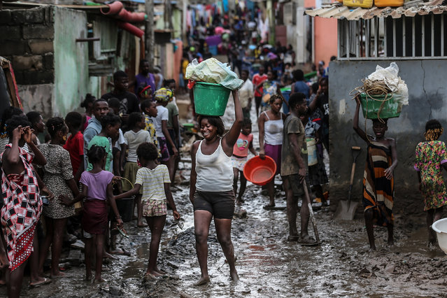 People on a muddy street after heavy rain that fell Monday night in Encide neighborhood, in the Sambizanga district, on the outskirts of Luanda, Angola, 20 April 2021. The torrential rains that hit Luanda on 19 April killed 14 people and left 8,000 displaced, with 16 houses collapsed, 15 trees fell, and a bridge was destroyed, among other damages yet to be calculated. (Photo by Ampe Rogerio/EPA/EFE)