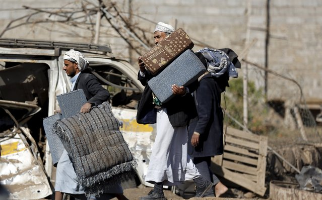 People carry furniture from their house after it was hit by a Saudi-led air strike in Yemen's capital Sanaa January 6, 2016. (Photo by Khaled Abdullah/Reuters)