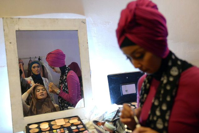 An Indonesian beautician (R) applies make-up on a contestant of the Muslimah World 2013 as they prepare for a grand final during the Muslimah World competition in Jakarta on September 18, 2013. (Photo by Adek Berry/AFP Photo)